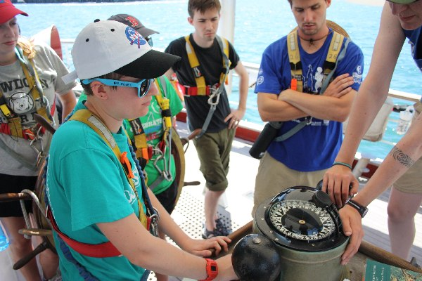 Kennedy from Wellesley College, Gabi from Bowdoin College, Ben from Williams, and Bennett from Oberlin learn how to mark their head using the steering compass from Williams-Mystic alum Jane McCamant S'04, who is the ship's third mate.