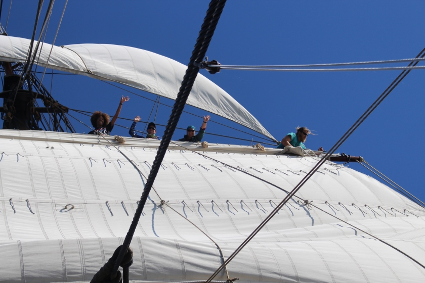 Students wave while furling a sail aboard a tall ship.