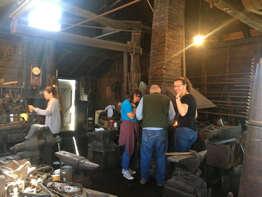 Students and an instructor work in a shipsmith's forge.