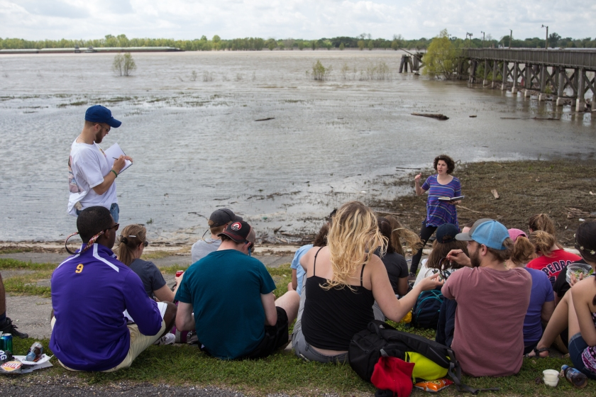 students sit on a Mississippi River levee