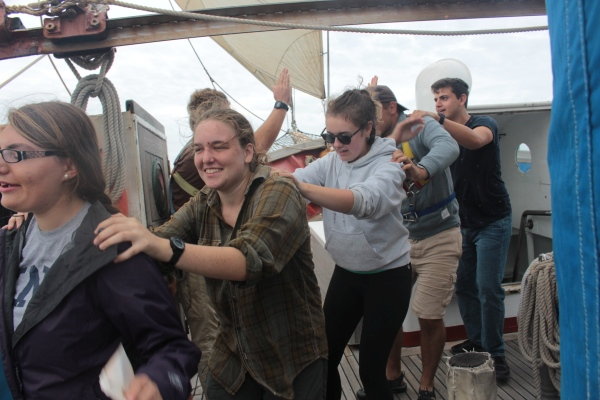 students in a conga line aboard a ship