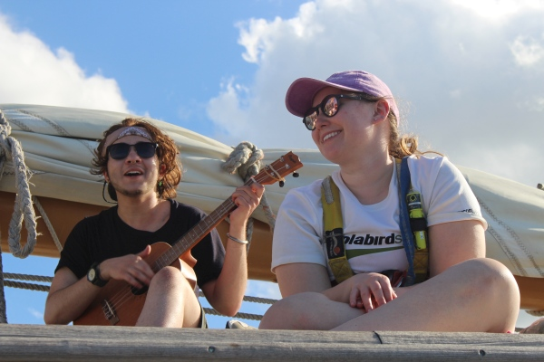 two students, one playing guitar, sing aboard a ship