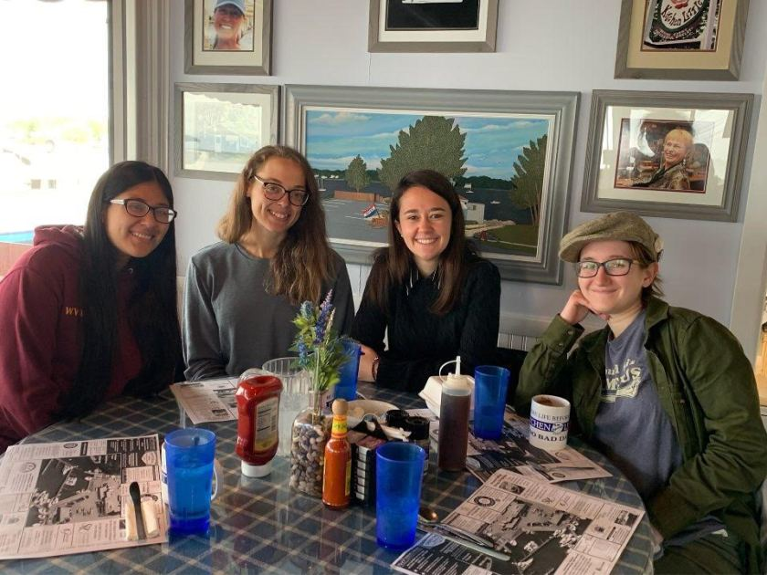 Picture shows four students smiling at a table in a breakfast restaurant