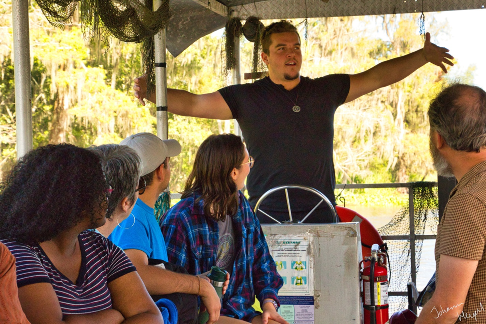 Image shows local tour guide ZZ Loupe gesturing at the helm of a pontoon boat in the bayou, while Williams-Mystic students look on