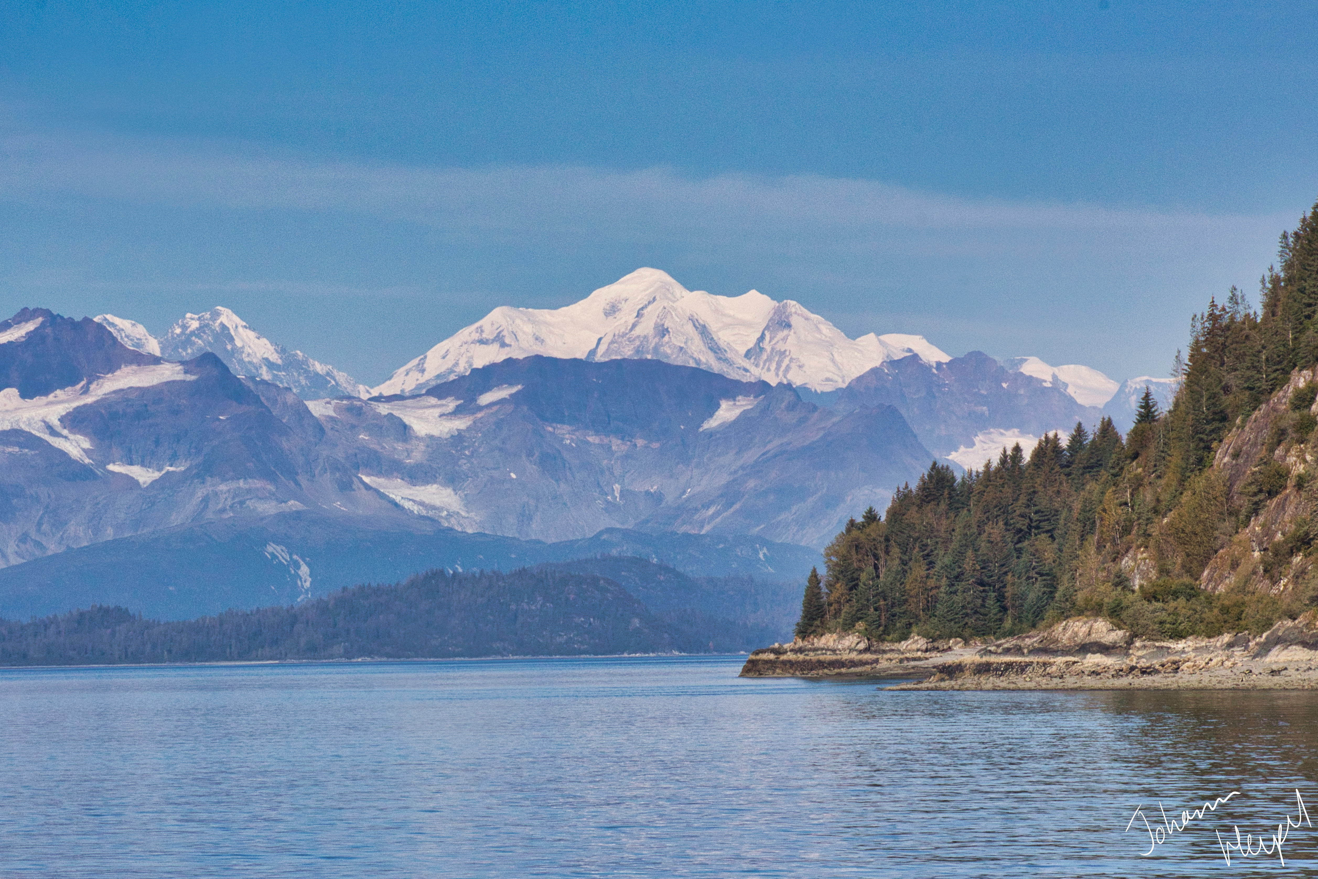 Photo shows snow-capped mountains towering over a pristine bay, with a rugged, evergreen forest on its shores