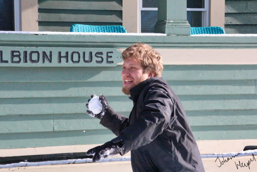 image shows a Williams-Mystic student grinning as he hurls a snowball in front of Albion House