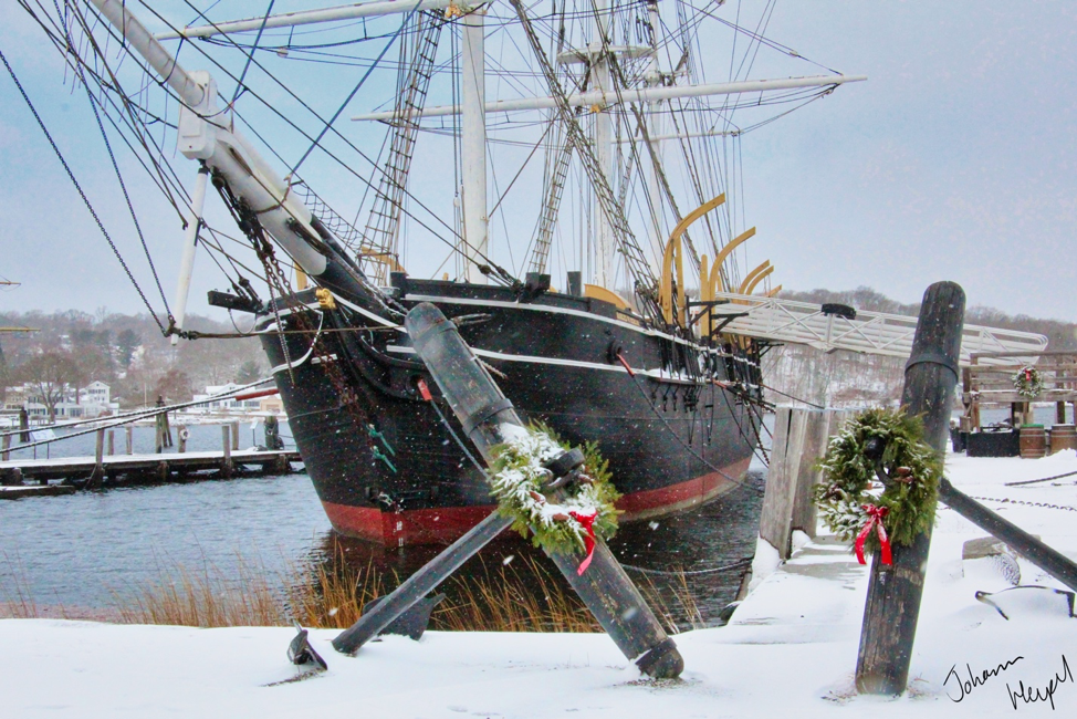 image shows the Charles W. Morgan, a large nineteenth-century whaling ship at the Mystic Seaport Museum, on a snowy day, with wreaths festooning decorative anchors place along the shore