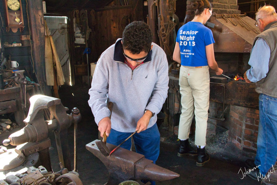 Image shows a student hammering a red-hot piece of metal on an anvil in a historic forge, with another student firing metal in a hand-operated forge in the background