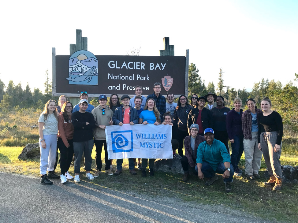 Image shows the Class of Fall 2019 posing with a banner reading Williams-Mystic. Behind them is a sign reading Glacier Bay National Park and Preserve, and behind that is a pine forest