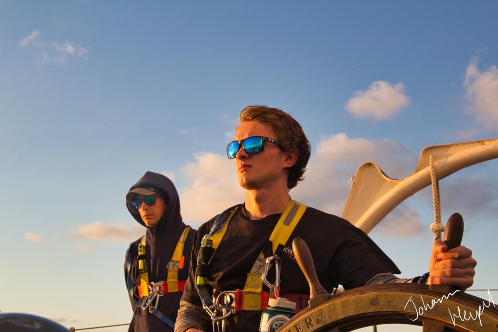 Picture shows a student at the helm of a sailing ship near sundown