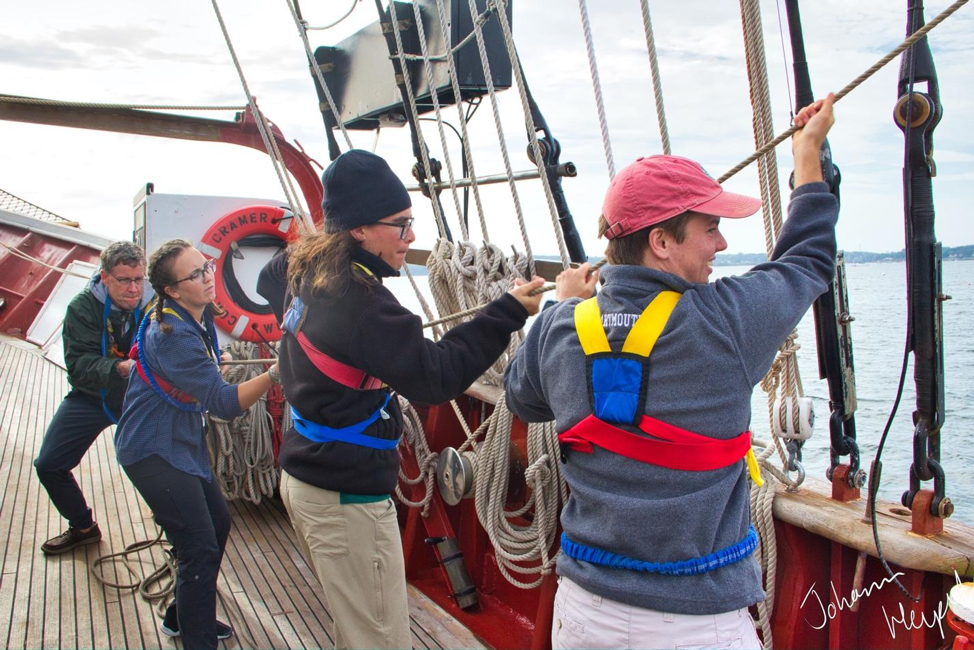 Images shows students hauling on a rope aboard a sailing ship
