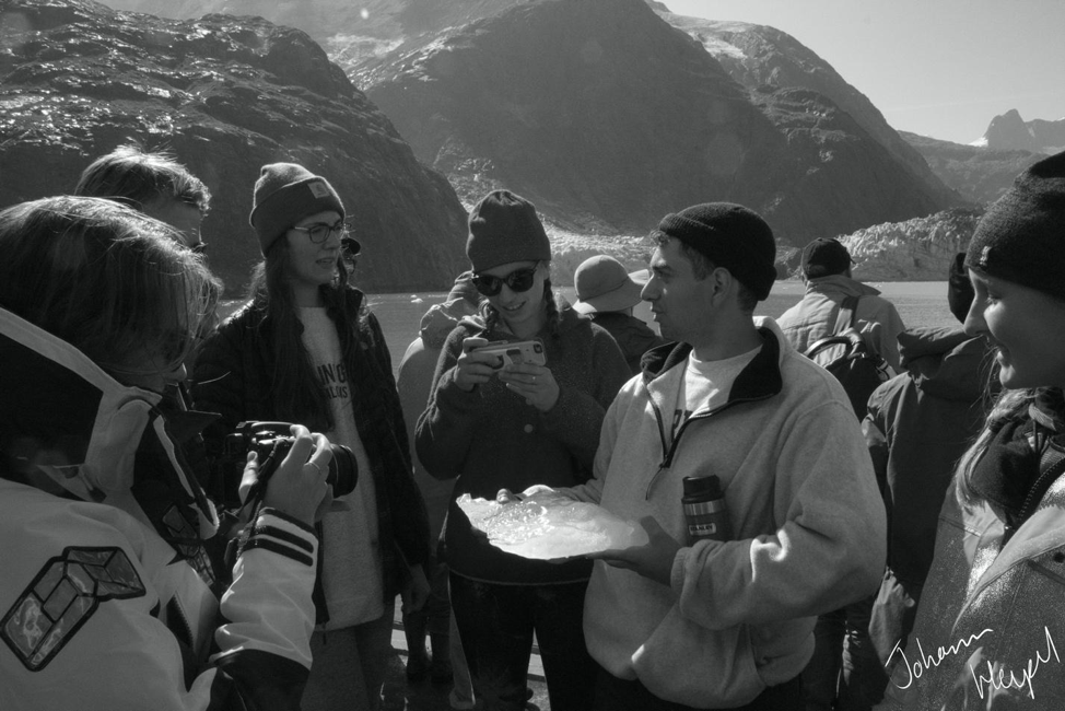 Picture shows a student holding a large chunk of glacial ice aboard a boat. Other students crowd around him, while rocky mountains and glaciers fill the background.