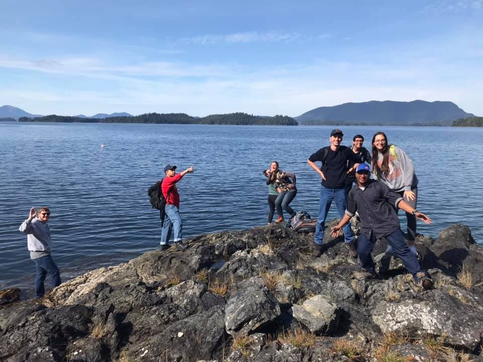 picture shows students clambering on a rocky shore, posing and grinning in front of a pristine bay with evergreen forests and mountains in the background