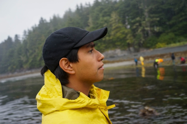 Image shows a student in a bright yellow rain jacket, looking off into the distance. He is standing in a small cove, with an evergreen-lined shore and other rain-gear-wearing students in the background.