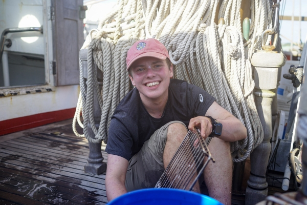 Image shows a grinning student sitting on the deck of a ship. He is holding up what appears to be a grill rack, and you can just barely see a large bucket in the foreground. Behind him, there is a series of coils of rope — lots of rope.