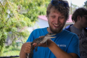 Image shows a grinning student holding a baby alligator. The gator's body is about a foot long; it's mouth is slightly open to reveal minute, razor-sharp teeth.