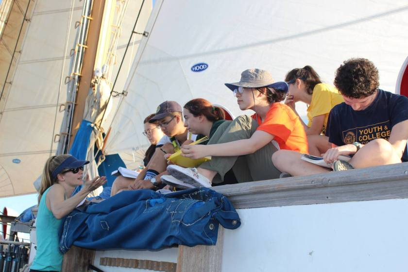 Image shows a group of students on the deck of a ship. They are focused on their journals or on a woman who stands in front of them gesturing as she lectures