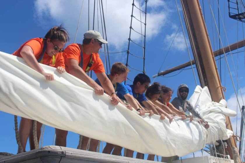 Picture shows a group of students arranged in a line behind a furled sail. They bend forward to pull the furled sail into a tight bundle. In the background, the masts rise out of the frame and into bright blue skies.