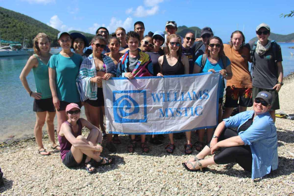 "Picture shows a grinning group of students posing on a tropical beach with a banner that reads ""Williams-Mystic."""
