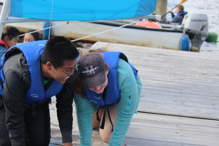 image shows two students laughing as they crawl onto a dock while wearing life jackets