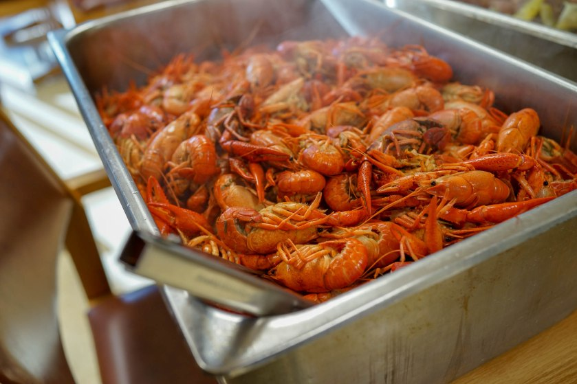 image shows a steaming tray of boiled crawfish