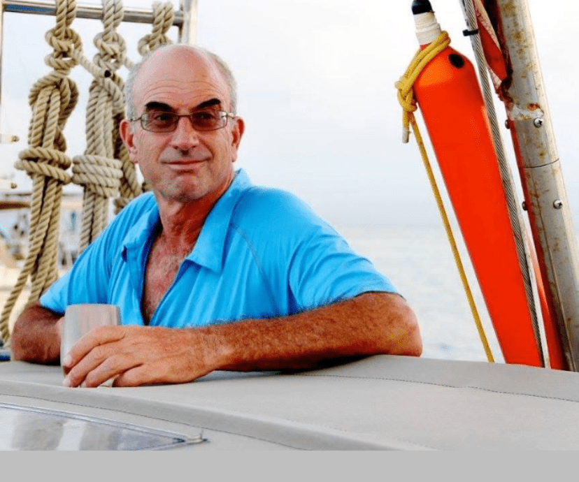 Image shows Eric smiling aboard a small sailing vessel, evident from the lines neatly pinned and coiled behind him. He is wearing sunglasses