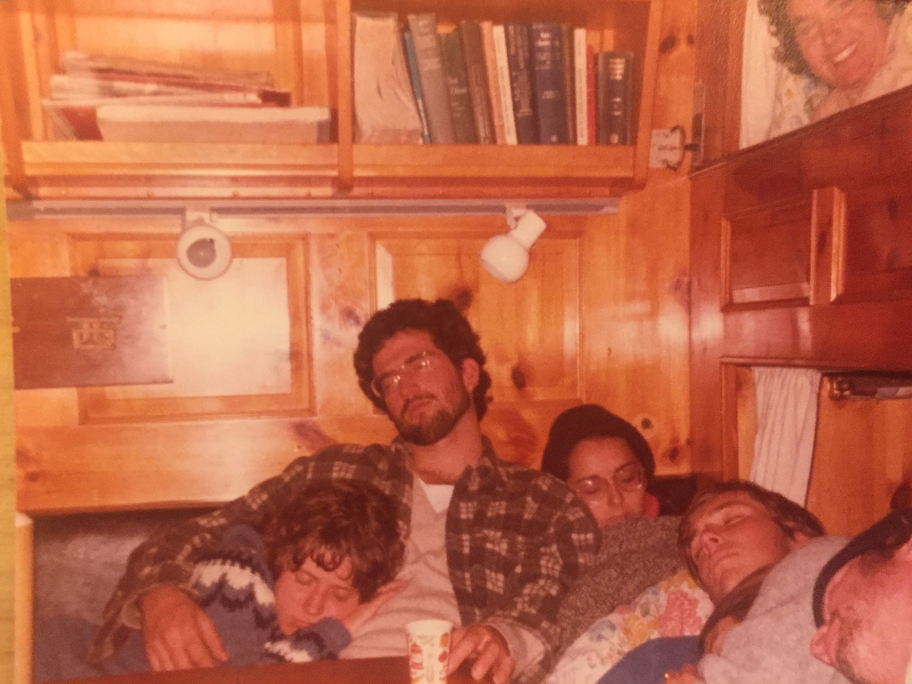 Image shows three college students slumped side by side, napping in a cozy, wood-paneled nook belowdecks, with two bunks just visible in a wall to the right