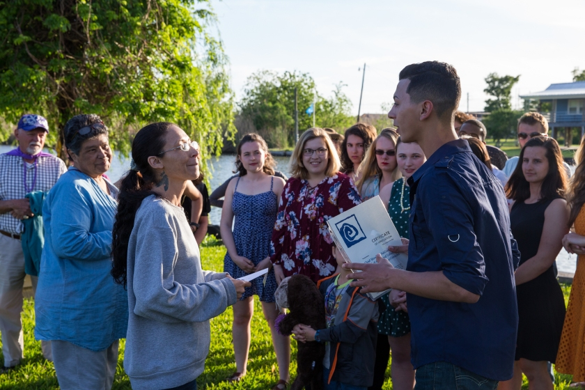 image shows a woman listening to a student with a piece of laminated paper in his hands; in the background, students and others look on. The group is at the edge of a verdant bayou